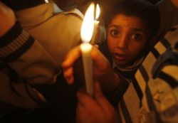 A boy holds a candle during a protest against the blackouts in Gaza. Photo: Reuters