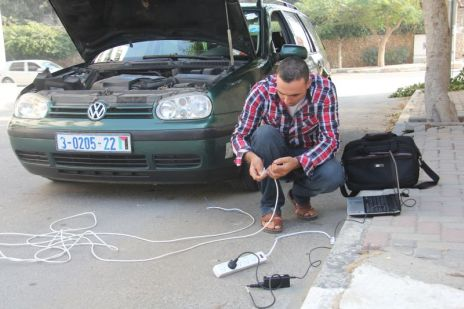 Charging a laptop with a car battery. Photo: Khaled Al Ashkar for Gisha